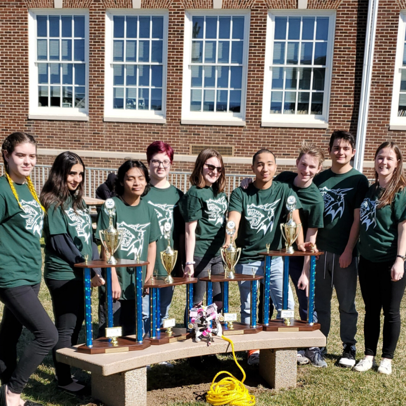 DV SeaPerch Team pose on school lawn with their ROV and 4 trophies