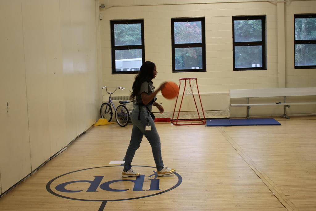 Staff member bouncing basketball
