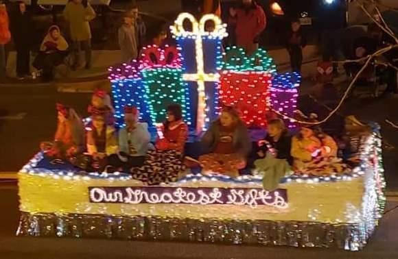 Float with students seated in front of packages outlined with lights