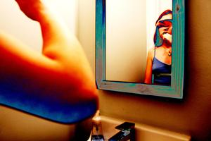 photo of girl looking into mirror while brushing teeth