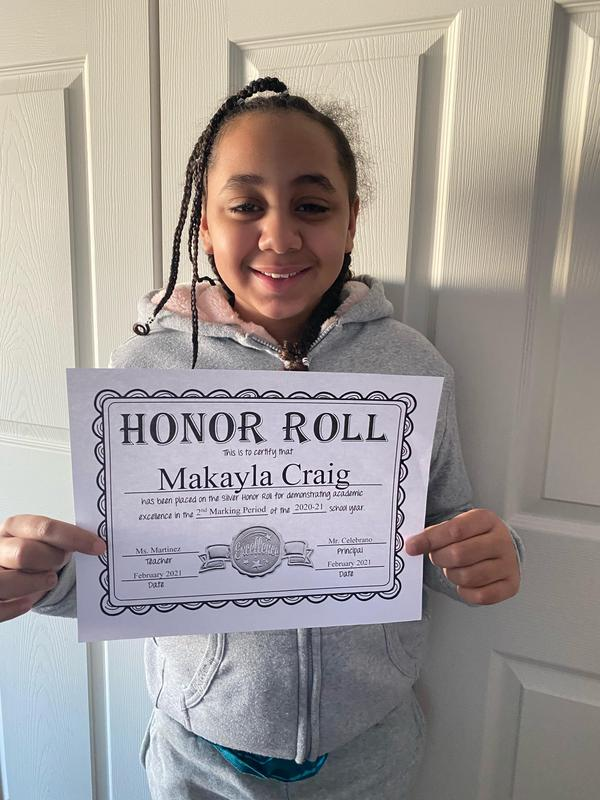 Makayla C. holding honor roll certificate