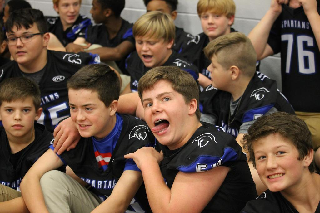 Group of football players sitting on floor