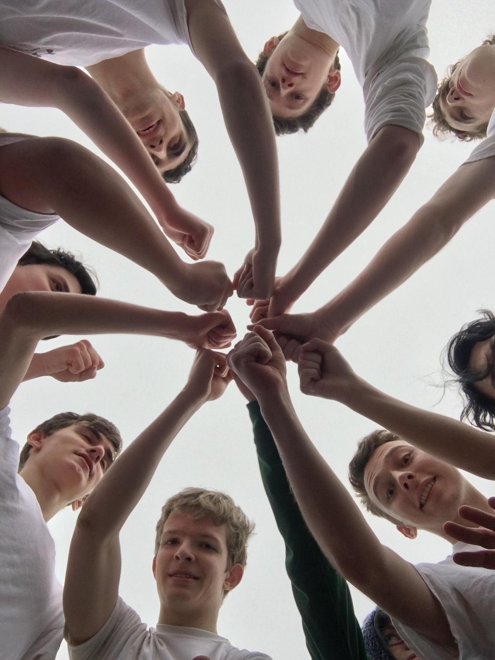 Ultimate Frisbee team members put their hands in