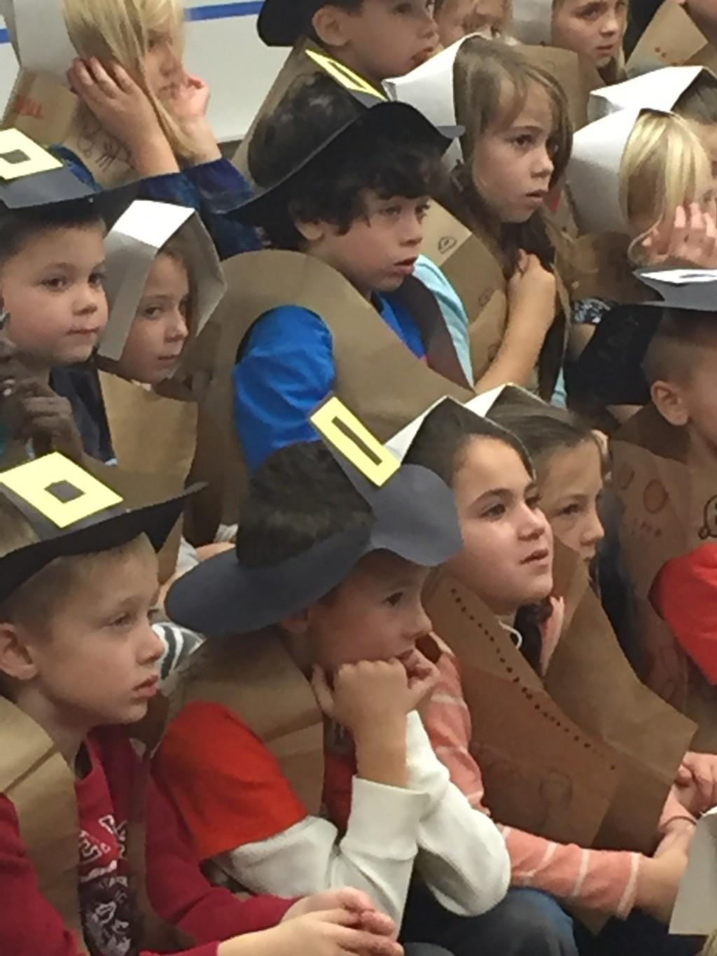 students dressed as Pilgrims listen to story