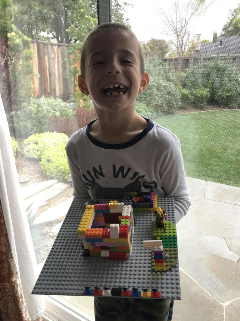 picture of boy holding platform with a lego house he built on it