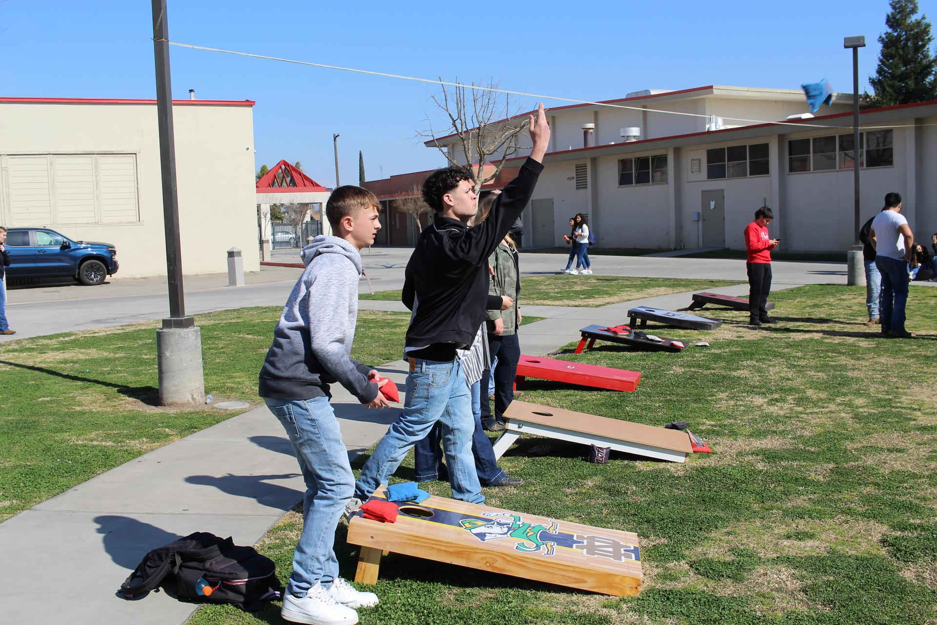 students and teachers playing cornhole