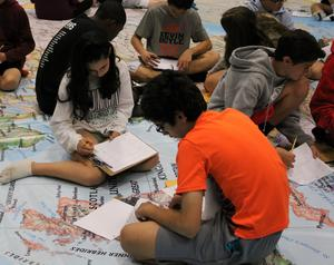 In a geo-scavenger hunt, of sorts, students used latitude and longitude to find an assigned location on the National GeographicGiant Map, set up in the schools' gymnasiums. Once at the location on the map, the students found an envelope with instructions on how to proceed with their lesson on European History.  Pictured here is a student studying on the Giant Map.