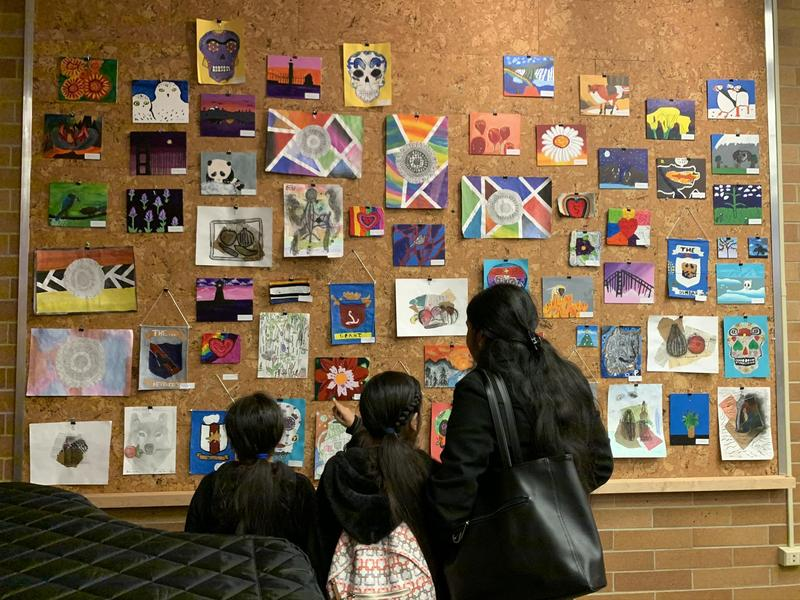 patrons viewing student art at caldwell library