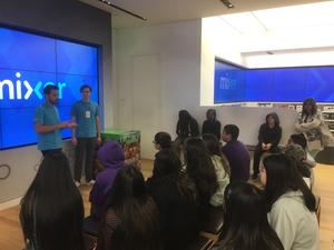 students seated looking at an instructor in the front of the room who is standing in front of a screen