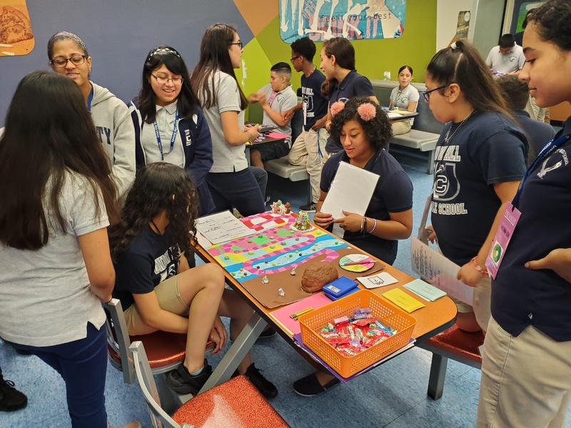 group of girls around the table playing the game they created