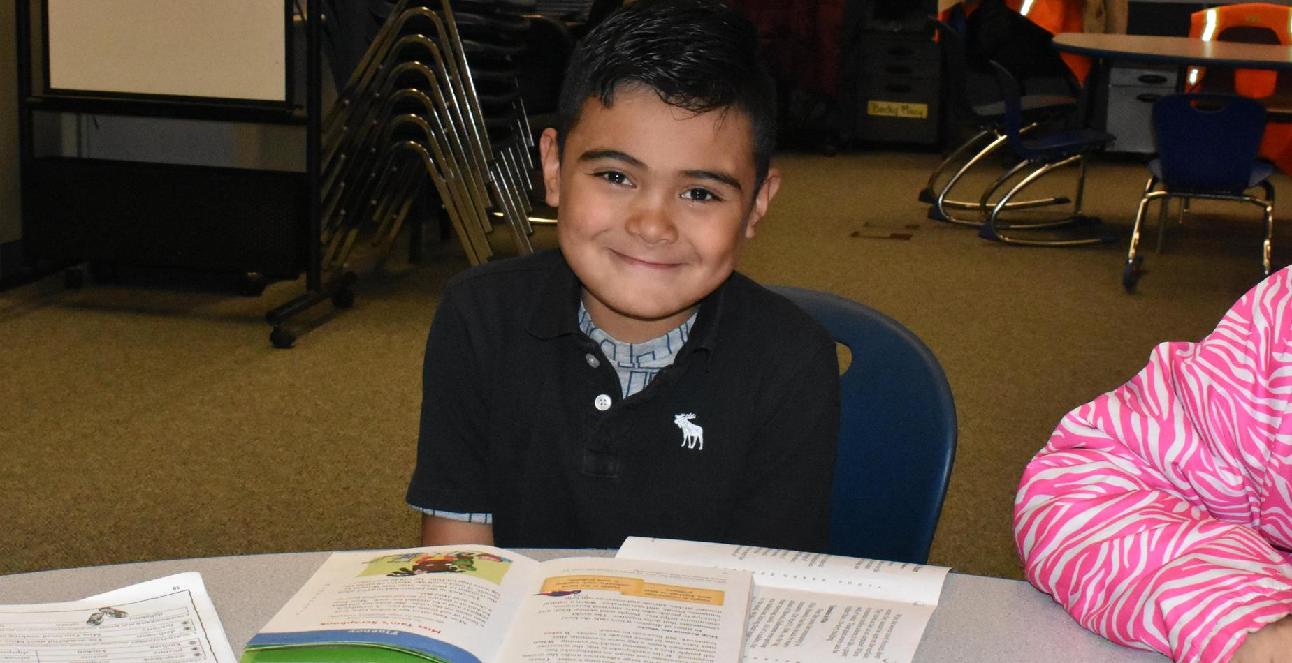 A boy getting ready to read during reading group.