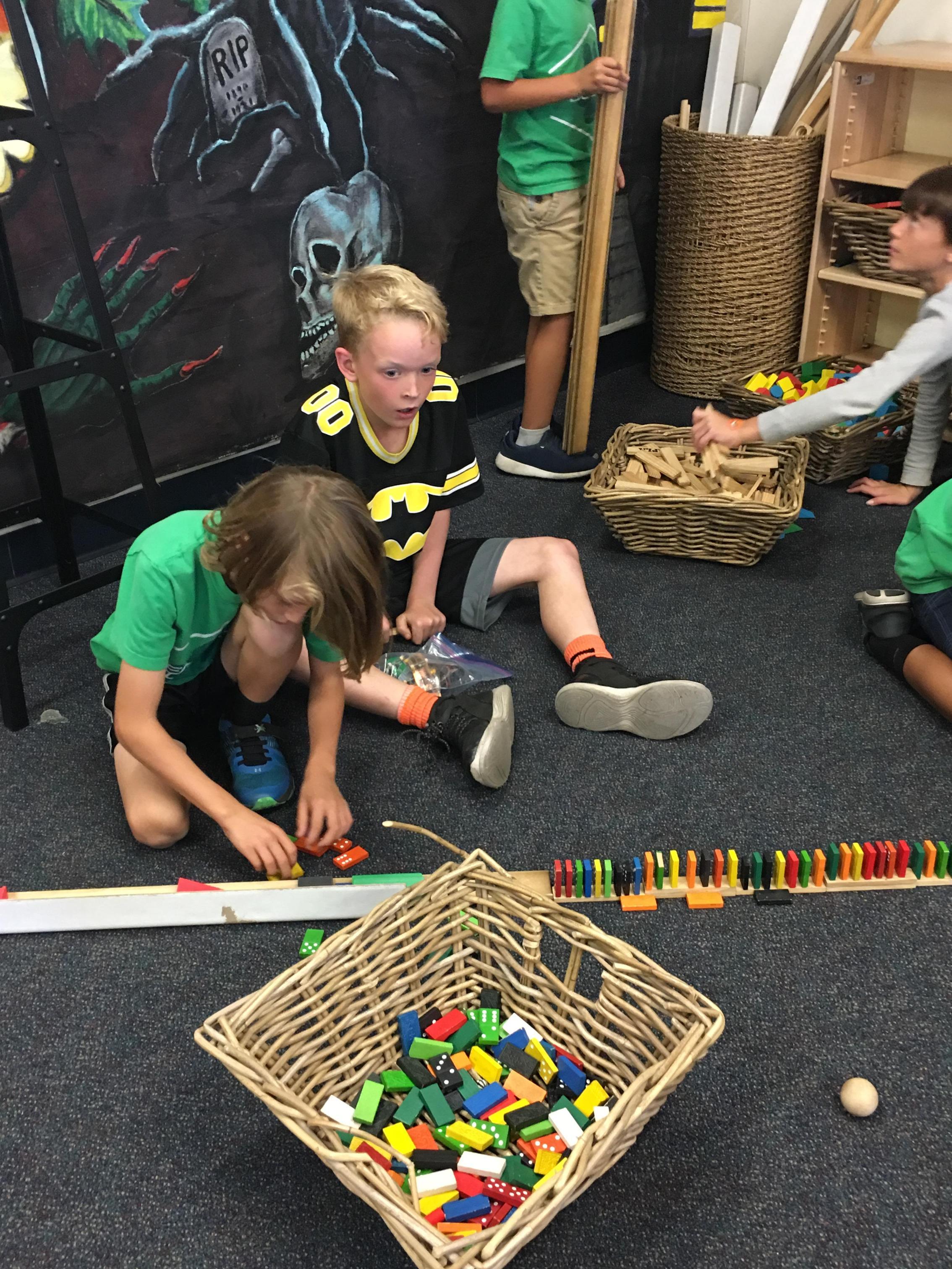 3 children building with dominoes