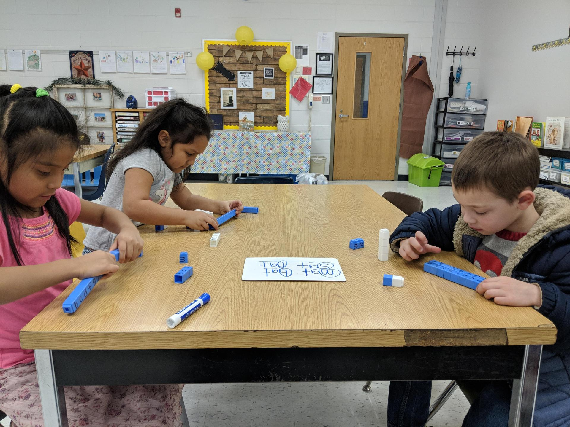 Kindergarten busy putting letters together to build words.