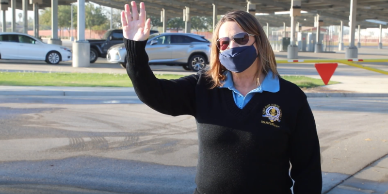 Transportation employees waves to students getting off of the bus