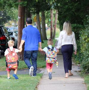 Photo of back of family walking to school on first day.