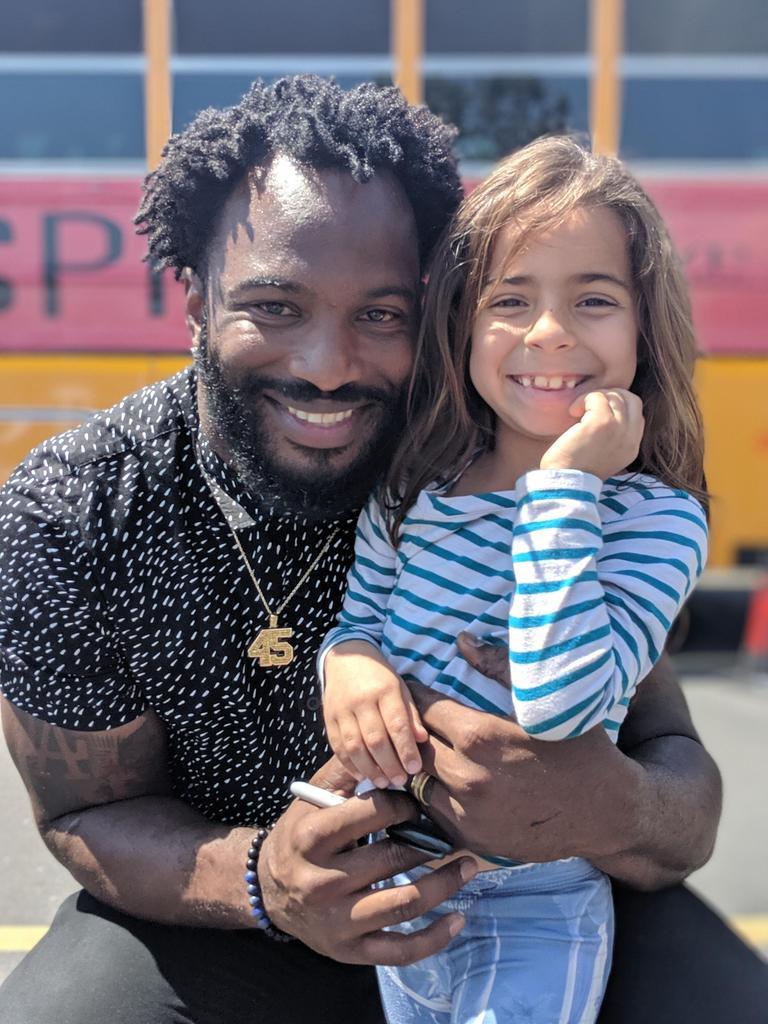 football player Marcel Reece hugs first grader