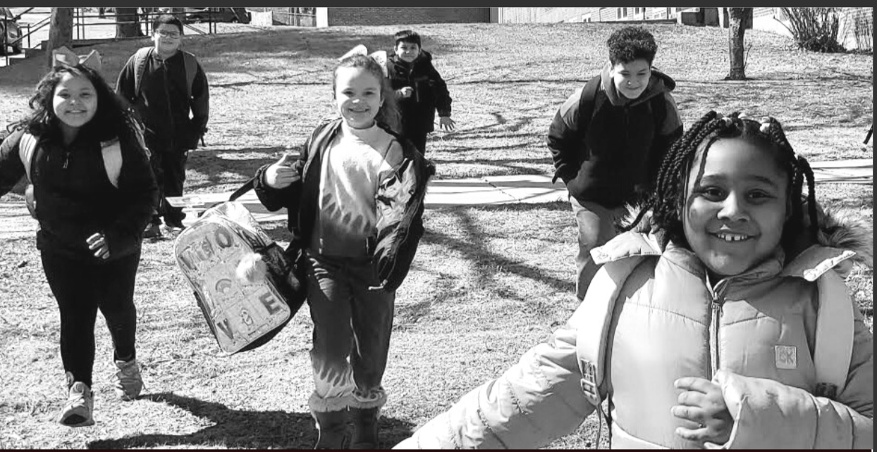 black and white photo of students with backpacks outside