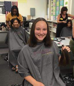 Photo of RIS student holding lock of hair after a stylist cuts it to donate for wigs for children and teens with cancer and other disorders.
