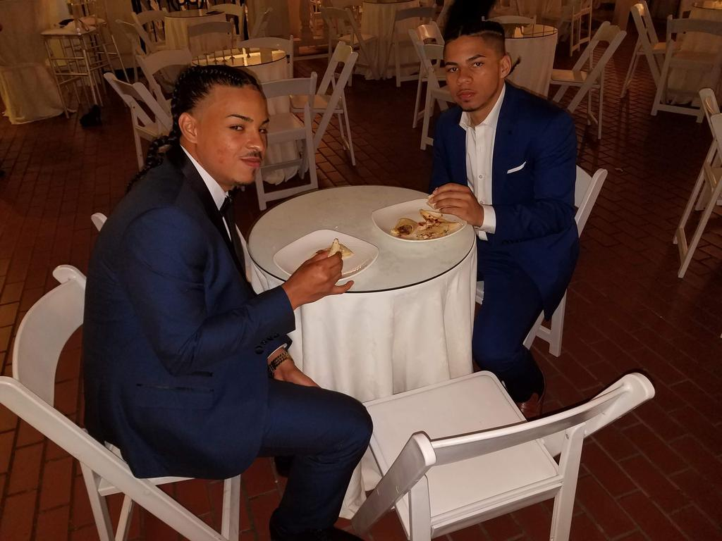 Two suited students eating at a table