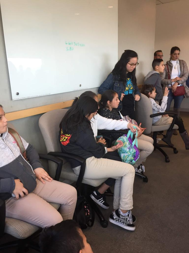 students sit in chairs in conference room at city hall