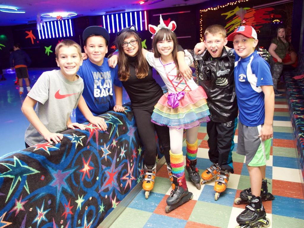 kids in Halloween costumes pose at roller rink