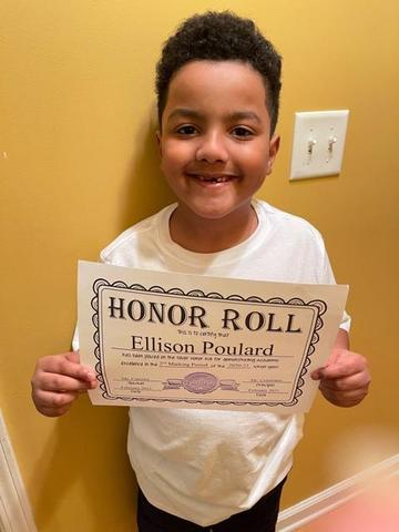Ellison holding honor roll certificate