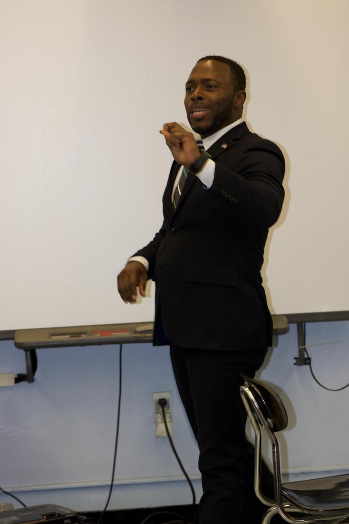 a suited man giving a lecture