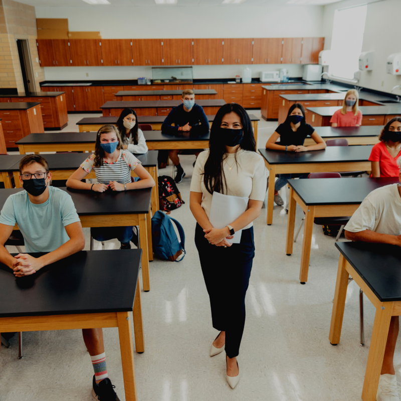 students seated at tables in facemasks and teacher standing in center in facemask