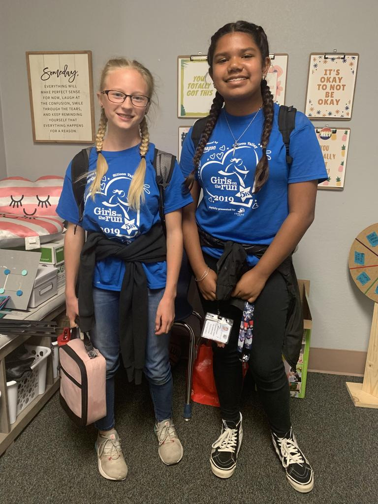 "Two students wearing ""Girls on the Run 5k"" t-shirts for twin day."