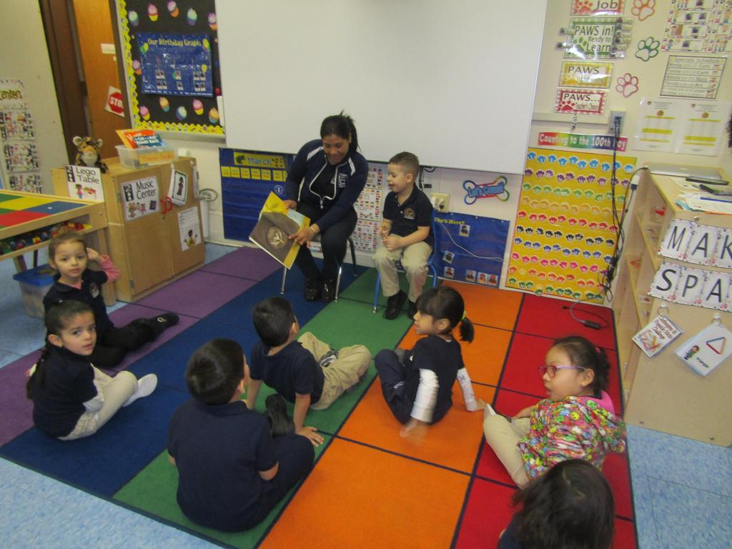 mother reading to kids sitting on class rug