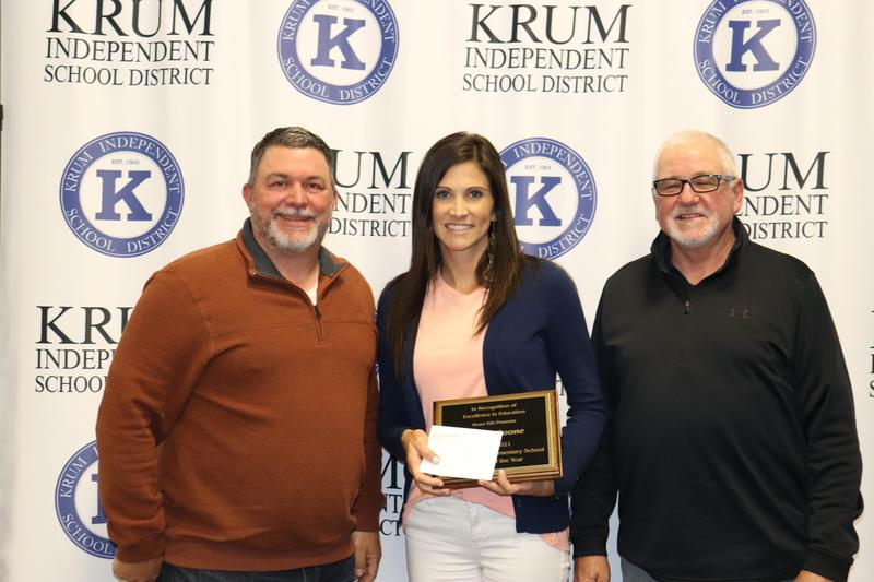 megan boone stands with board president eric borchardt and board vp terry knight as they present her with her teacher of the year plaque