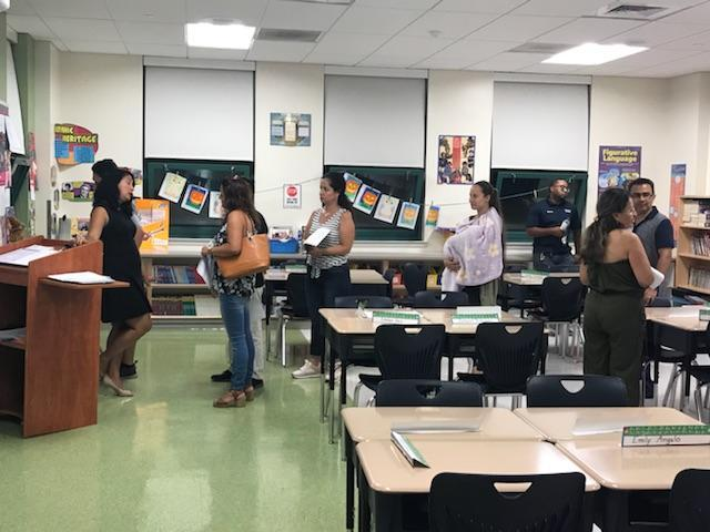 teacher answering individual parent questions after presentation