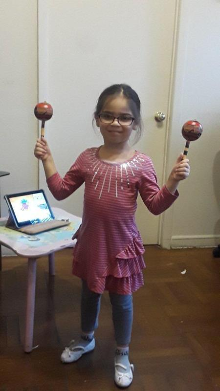 girl with glasses holding maraca's in her hands