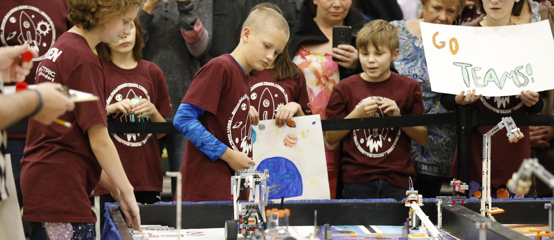 elementary students in matching maroon shirts run their robot in Lego League