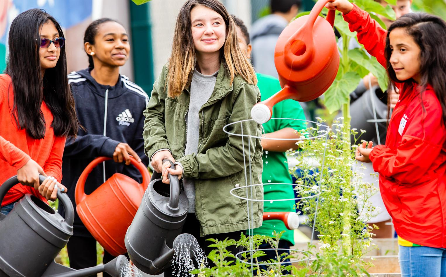 A group of students water plants during their outdoor class.