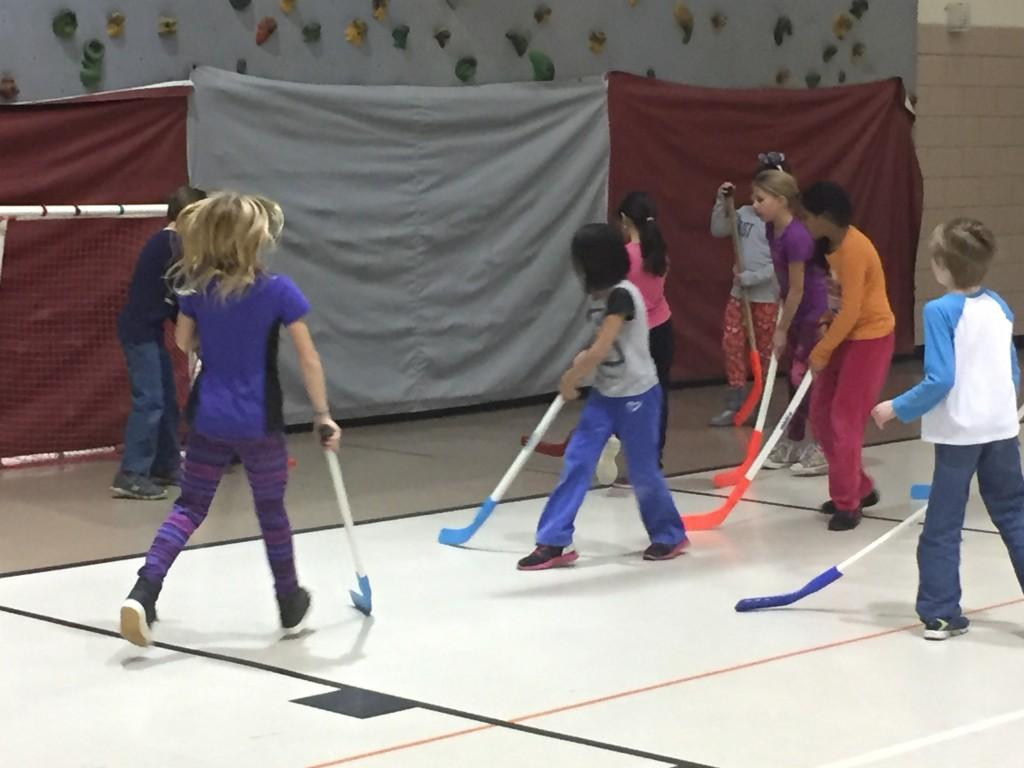students play hockey in gym class
