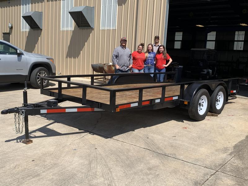 a group of girls from FFA organization standing next to a trailer they built