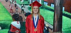 AHS senior girl in cap and gown in front of artwork