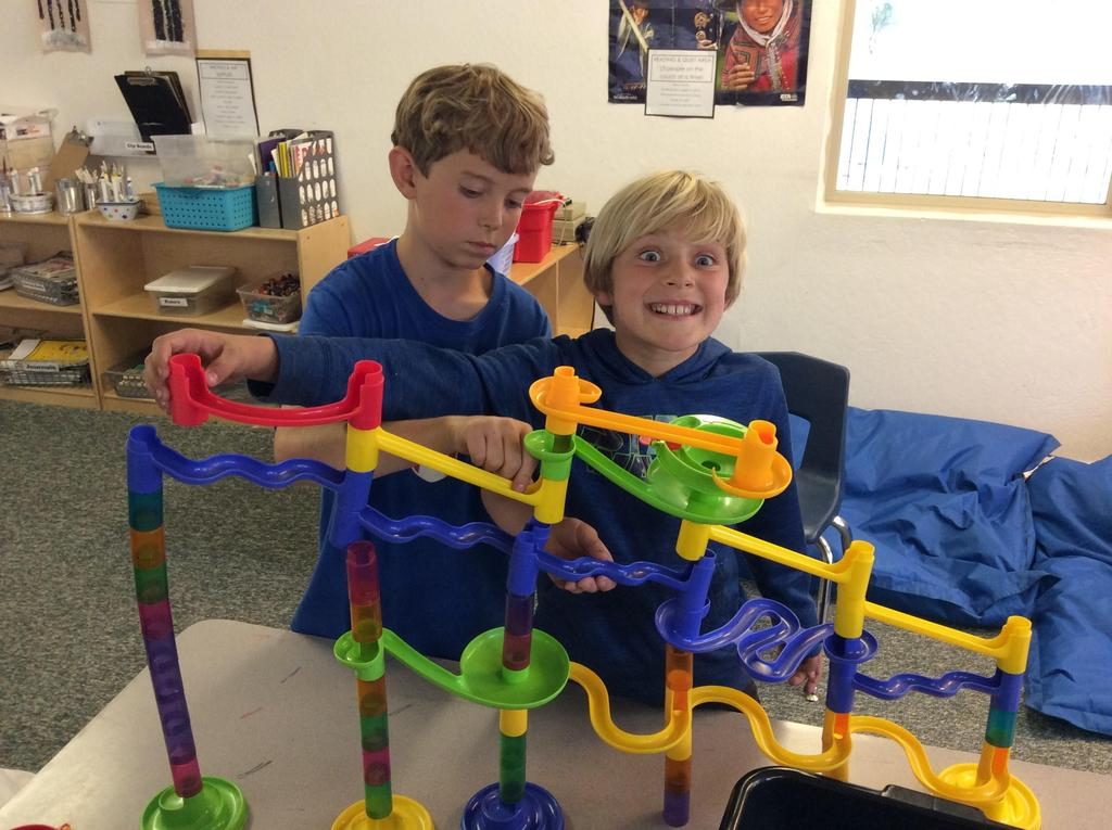 boys playing marble track