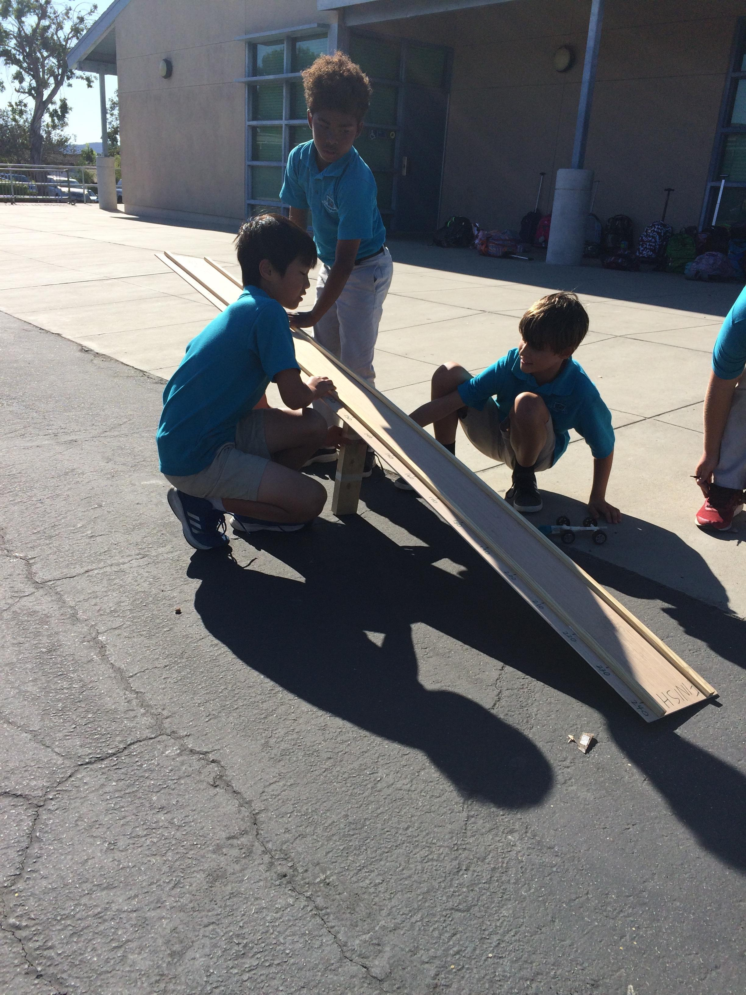 three students lifting the track so the balloon car travels faster and farther