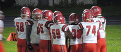 Varsity football team in uniform in a huddle on the field during a game.