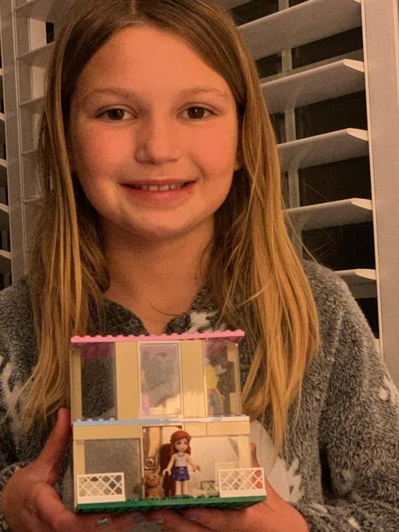 girl holding lego house she built