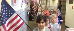 Students lined up in a parade walking in hallway