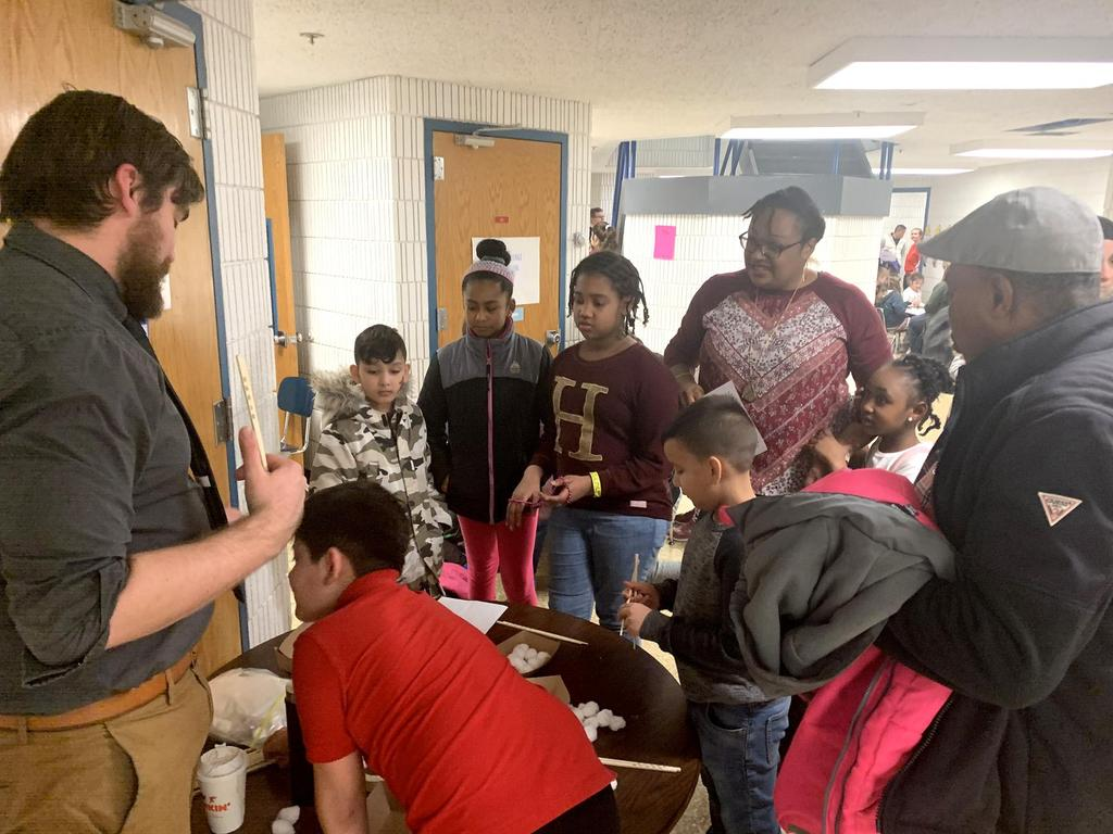 Students and adults huddle around a crafts table