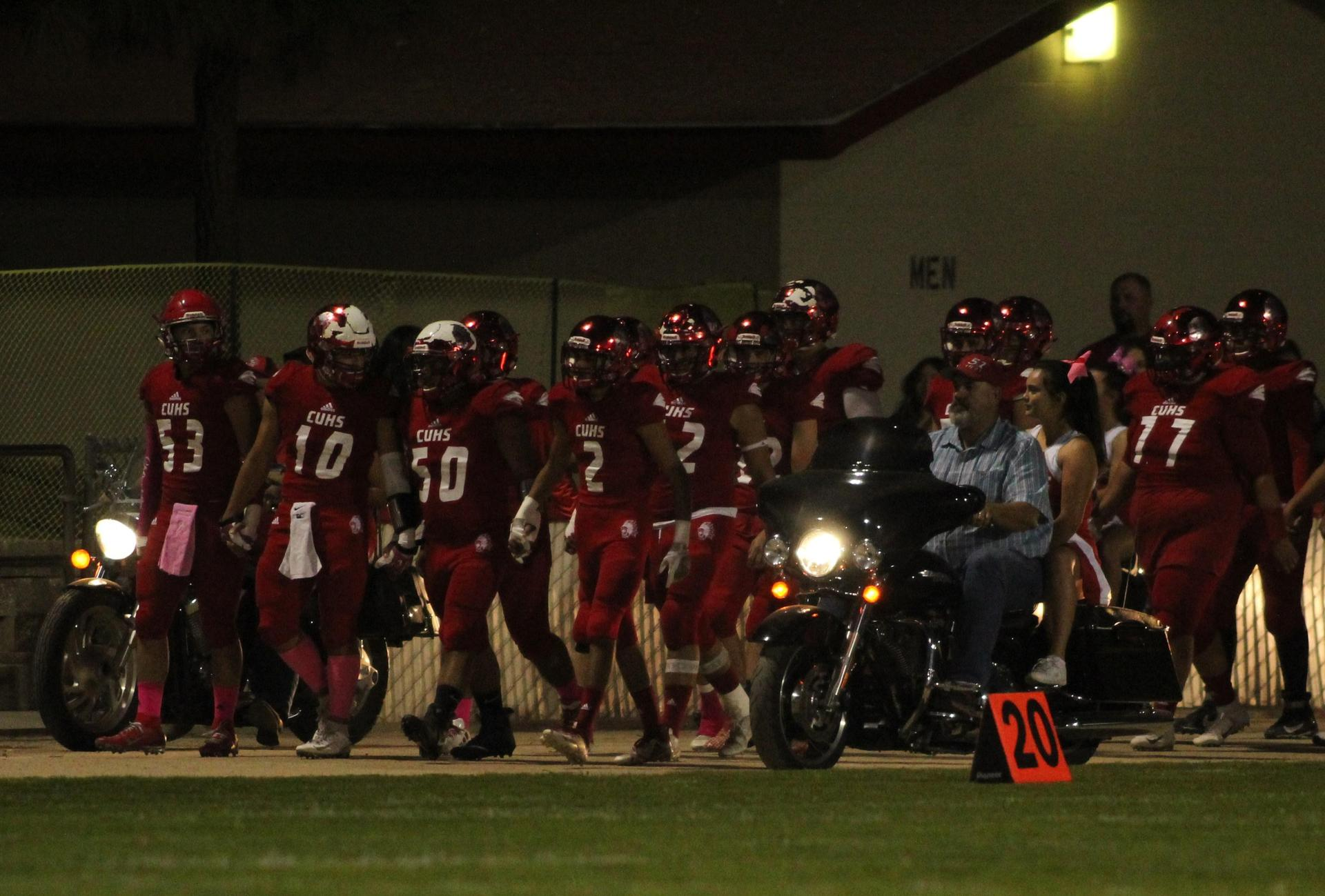 Varsity football players, cheerleaders, and chain gang workers at football game against Yosemite