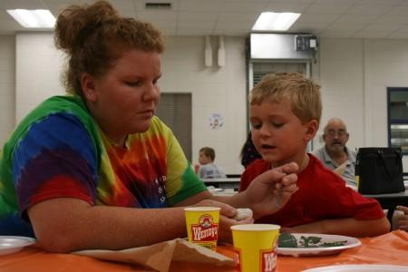 Mrs. Waldrop is helping a student paint rocks for Tifton Rocks.