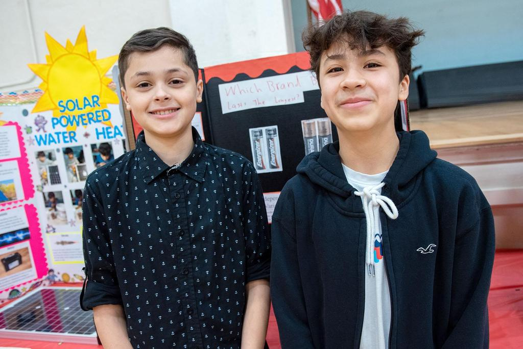 Two students stand in front of their project