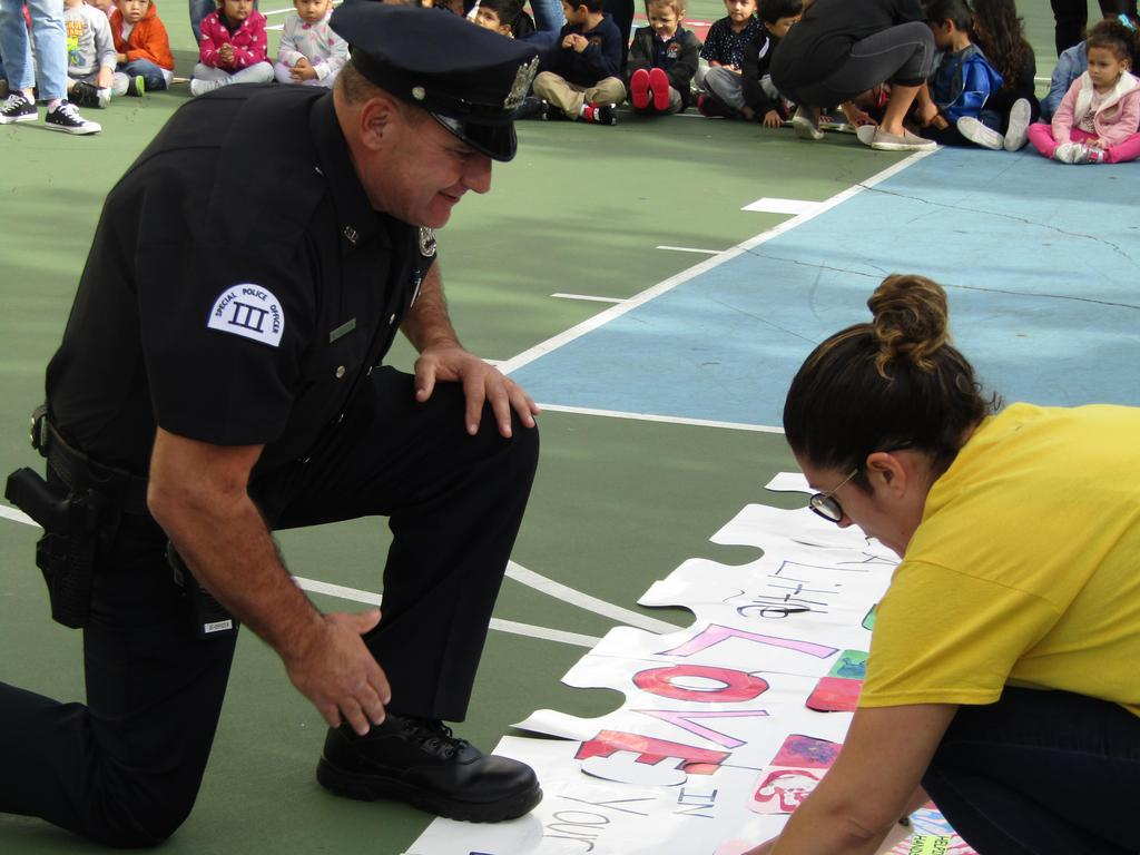 UC police officer placing his piece of the puzzle