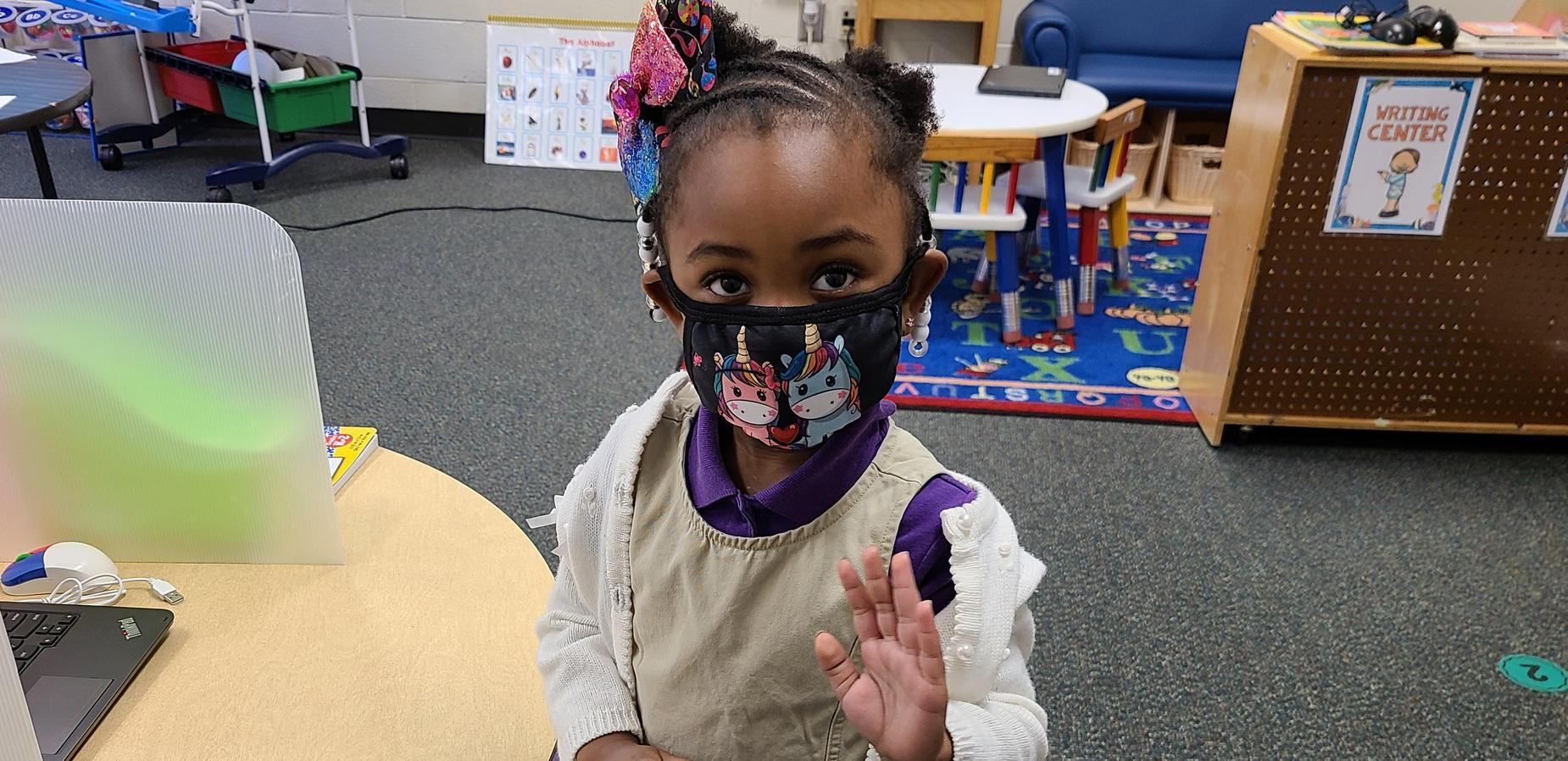 A child development student waving.