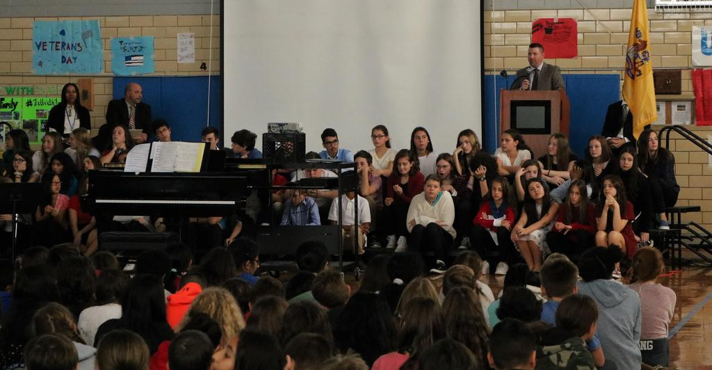 Photo of Edison principal Matthew Bolton speaking during Veterans Day assembly.